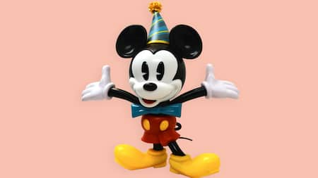A Mickey Mouse figurine wearing a birthday hat