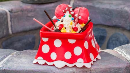 A Minnie Mouse themed dessert with ice cream served in a polka dot container