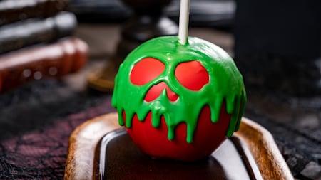 Manzana de caramelo rojo en forma de calavera con salsa verde que gotea