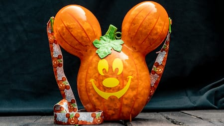 A Mickey Mouse shaped pumpkin bucket full of popcorn
