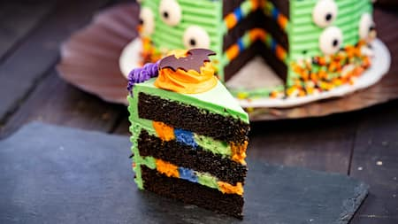 A slice of chocolate cake with multicolored frosting
