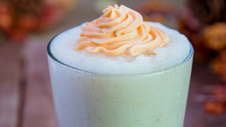 A frothy drink topped with orange whipped cream