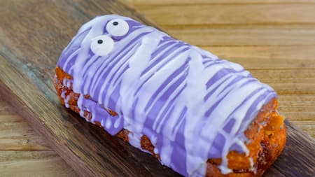 A peanut butter donut covered in purple frosting
