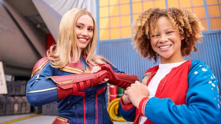 Captain Marvel and a fan pose heroically outside a hangar