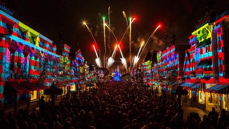 A crowd of people gather along Main Street U.S.A. as fireworks burst over Sleeping Beauty Castle
