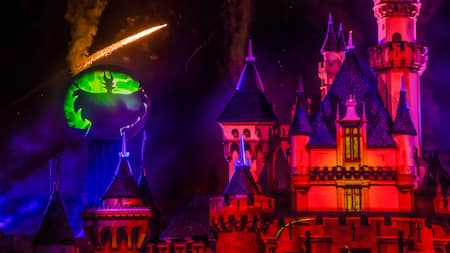 Sparkles fly in the night by a large projected image of Maleficent, next to Sleeping Beauty Castle during Halloween Time at the Disneyland Resort