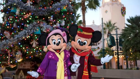Mickey Mouse and Minnie Mouse in holiday attire, posing in front of a Christmas tree