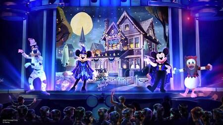 Una representación artística de Goofy, Minnie, Mickey y Donald en el escenario con disfraces de Halloween