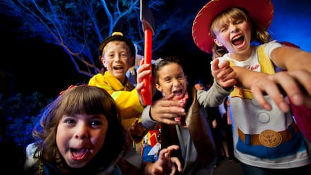 Four costumed kids making silly facial expressions