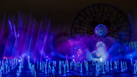En una gran fuente se proyectan chorros de agua que se disparan hacia el aire como una animación de Shelley Marie y Ursula durante el espectáculo nocturno Villainous
