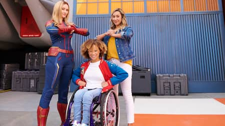 Captain Marvel and fans pose heroically outside a hangar