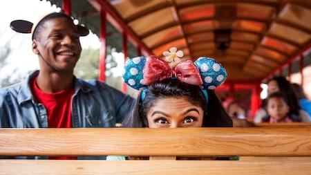 Un Visitante que viste un sombrero de Minnie Mouse se esconde juguetonamente detrás de un asiento en un paseo en tranvía