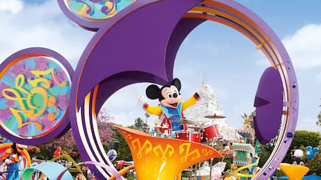 Mickey Mouse plays bandleader from a parade float in the famous shape of his head