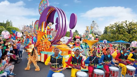 Drummers play snares in front of a parade float with Mickey Mouse, as Goofy interacts with the crowd