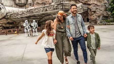 A family at Star Wars: Galaxy's Edge, with First Order Stormtroopers and the Millennium Falcon in the background