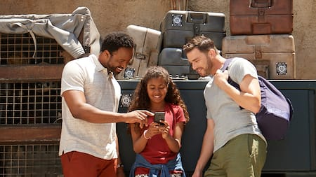 Two men and a girl reading the latest notification inside of Star Wars: Galaxy's Edge
