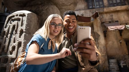 A man and woman reading the latest notification inside of Star Wars: Galaxy's Edge