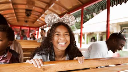 A girl wearing Minnie Mouse headgear seated in a trolley