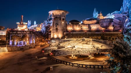 The Millennium Falcon docked below exotic Star Wars buildings and petrified wood spires