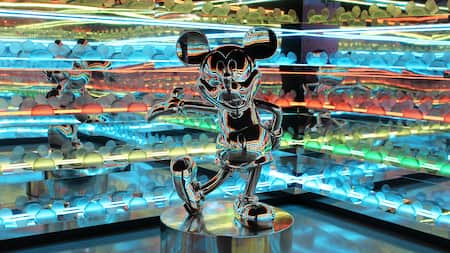 A metallic statue of Mickey Mouse in a room with mirrors and colored lights