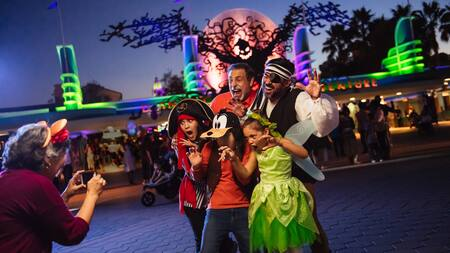 Grandma snaps pics of grandpa, dad and 3 kids in Halloween costumes near the Disney California Adventure Park entrance with Oogie Boogie and bats overhead