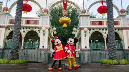 Dressed in Asian inspired costumes, Mickey and Minnie stand arm in arm near a Paradise Gardens Park building decorated with festive Lunar New Year lanterns