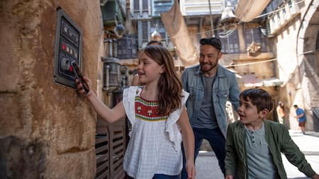 At Star Wars Galaxy's Edge, a tween girl scans a wall panel with her phone as her dad and brother watch