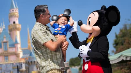 A man holds a smiling baby near Mickey Mouse and Sleeping Beauty Castle