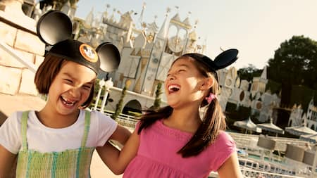 2 girls laugh while wearing Mickey Ears