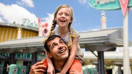 Una niña sonriente sentada en los hombros de un hombre cerca de Flos V8 Cafe