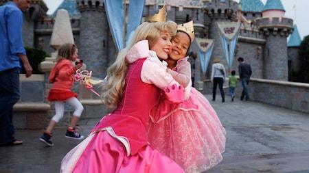 La Bella Durmiente abraza a una niña sonriente en frente del Castillo de la Bella Durmiente