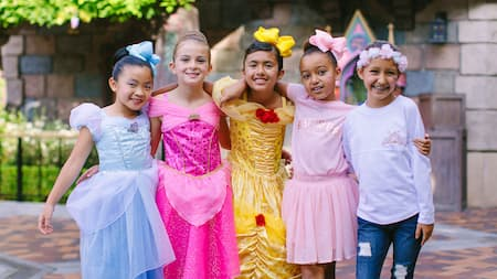 With their arms wrapped around each other, 5 young girls pose outside Sleeping Beauty Castle in princess costumes and accessories.