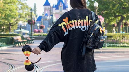 A Guest wearing a Halloween Disneyland shirt holds candy corn themed ears
