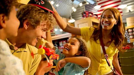 A happy family tries on hats in a Disney merchandise store