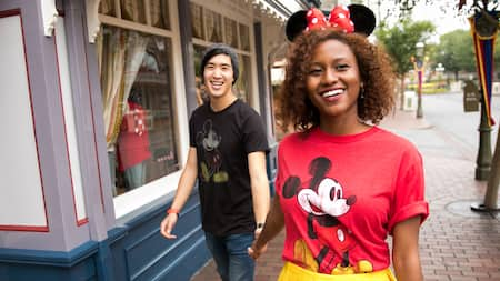 A couple in Mickey and Minnie attire, holding hands