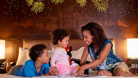 Una madre y sus 2 pequeños hijos comparten un momento feliz en su habitación de hotel