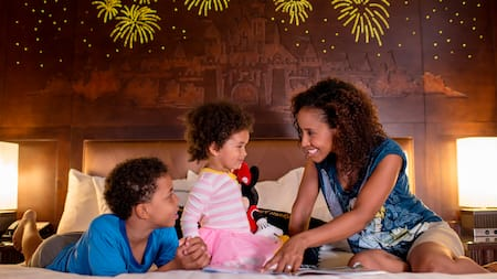 A mom and her 2 young kids share a happy moment in their hotel room