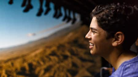 A teenager enjoying Soarin' Over California, with the legs of other Guests dangling above him
