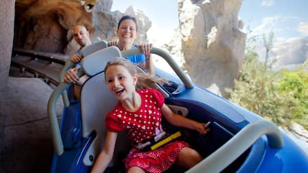 A girl and her parents ride the 3-person Matterhorn Bobsleds vehicles
