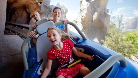 Una niña y sus padres pasean en los vehículos para 3 personas de Matterhorn Bobsleds