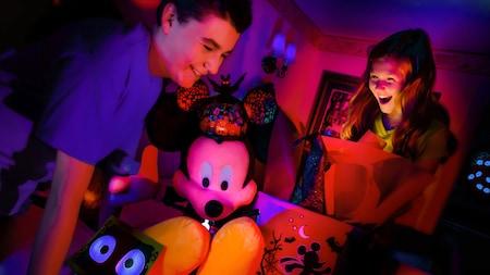 Dos niños abren con felicidad unos obsequios brillantes en su habitación de hotel, incluido un gran Mickey de Halloween de peluche