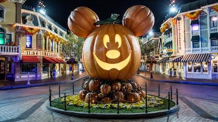 Una réplica gigantesca de una linterna tallada de calabaza con la cara de Mickey Mouse y dos calabazas más chicas sirviendo de orejas, en exhibición al final de Main Street U. S. A. en Disneyland Park
