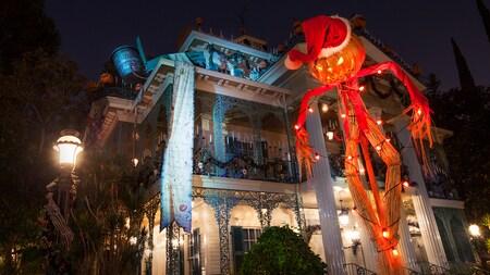 Un espantapájaros gigante delante de Haunted Mansion, parte de Halloween Time en Disneyland Park