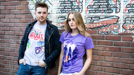 A young couple wearing Guardians of the Galaxy T shirts lean against a city street backdrop