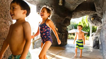 Three kids in swimsuits walking though a cave-like structure at Ketchakiddee Creek