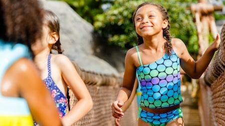 Une fille souriante en maillot de bains traverse la passerelle en bois