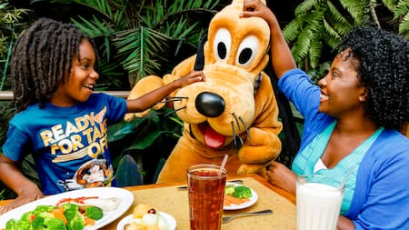 A girl and her mother sitting at a lunch table scratch Pluto's head