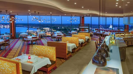 Interior of California Grill featuring booth, table and bar seating, floor to ceiling windows overlooking Walt Disney World Resort and more