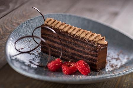 A piece of chocolate cake near 3 raspberries and a twist of chocolate