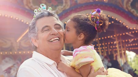 Prince Charming Regal Carrousel spins as a young female Guest kisses her grandfather on the cheek